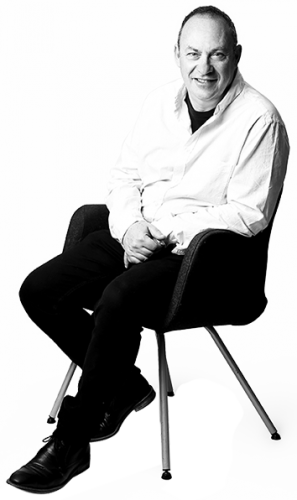 A full body image of Nicolas Brasch seated on a chair.